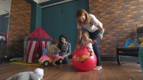 Mamme con il gioco dei childs La ragazza che salta su una palla rossa video d archivio
