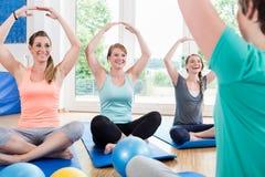Mammor i den postnatala tillbakagångkursen som gör yoga royaltyfri fotografi
