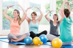Mammor i postnatal tillbakagång jagar göra yogaasana arkivfoton