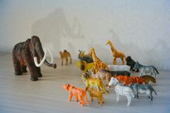 Mammoth ice age fighting with wild animals. Wild animals against a huge prehistoric mammoth royalty free stock photo