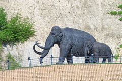 Mammouths, femelle et chiffres de petit animal Fait du métal, une partie d'une grande composition sculpturale Photos stock