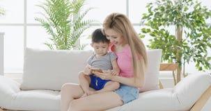 Mamusi use telefon z synem Zdjęcia Stock