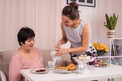 Mamy i dorosłego córka siedzi przy stołem i gawędzi pijący herbaty w domu Życzliwi powiązania między różnym fotografia stock