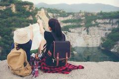 Mamy i dzieciaka mienia mapy i podróż plecaki siedzi zwycięskiego obszycie na uroczystym jarze Fotografia Stock