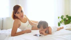 Mamy i syna dopatrywania smartphone w sypialni zdjęcie wideo