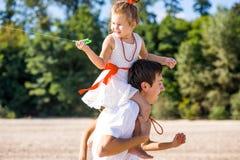 Mamy, tata i córki odprowadzenie na plaży, zdjęcie stock