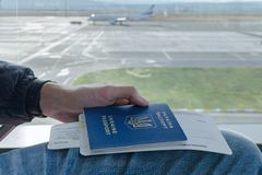 Man's手持与票的乌克兰外国护照到在背景停放的飞机的飞机 库存照片