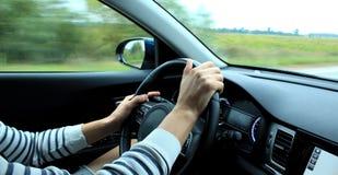 man's手的错误位置在快行车里面的方向盘 库存图片