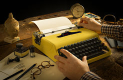 Man's递键入在一张木书桌上的葡萄酒黄色打字机 免版税库存图片