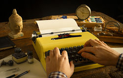 Man's entrega a datilografia em uma máquina de escrever do amarelo do vintage em uma mesa de madeira Fotos de Stock