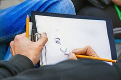 Man's-Hände mit Bleistiftzeichnung woman's Porträt Stockfotos