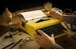 Man's händer som skriver på en tappning, gulnar skrivmaskinen på ett träskrivbord royaltyfri bild