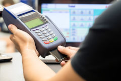 Man's hand with credit card swipe through terminal. For sale in store royalty free stock photography