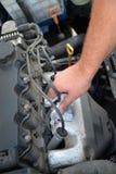 Man's-Hand, die Steckerverbindungsstück des Automotors entfernt Lizenzfreie Stockfotos