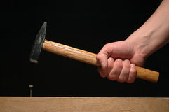 Man�s hand holding hammer moving to nail up the bo Royalty Free Stock Image