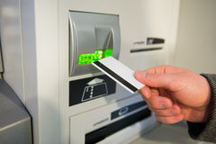 Man's hand puts credit card into ATM. Picture can be used in advertisement and websites royalty free stock images