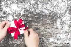 Man's hand som slår in den tomma gåvan för vit jul och binder pilbåge w Royaltyfri Foto