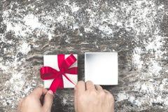 Man's hand som slår in den tomma gåvan för vit jul och binder pilbåge w Arkivfoto