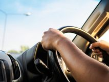 Man's hands holding steering wheel and road background. Drivin. G concept Royalty Free Stock Image