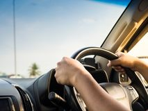 Man's hands holding steering wheel and road background. Drivin. G concept Royalty Free Stock Photos