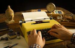 Man's passa la battitura a macchina su una macchina da scrivere gialla d'annata su uno scrittorio di legno Fotografie Stock