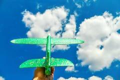 Man's ręka trzyma zielonego samolot przeciw niebieskiemu niebu w chmurach; pojęcie turystyka, podróż i wolność, zdjęcia royalty free