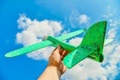 Man's ręka trzyma zielonego samolot przeciw niebieskiemu niebu w chmurach; pojęcie turystyka, podróż i wolność, zdjęcie stock