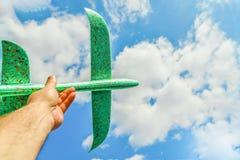 Man's ręka trzyma zielonego samolot przeciw niebieskiemu niebu w chmurach; pojęcie turystyka, podróż i wolność, fotografia royalty free