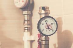 Manômetro do sistema de encanamento center com o torneira vermelho na tubulação de água plástica do sistema de encanamento Imagem de Stock Royalty Free