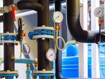 Manômetros e termômetro, tubulações e válvulas do torneira do sistema de aquecimento em uma sala de caldeira imagens de stock royalty free