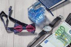 3Man香水,有黑皮带的手表,蝶形领结,笔记本 免版税库存照片
