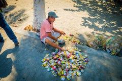 Man återanvändning av tomma cans i gatan, Colombia arkivfoto