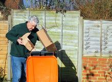 Man återvinningavfall eller racka ner på i fack Fotografering för Bildbyråer