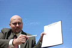 A man with а checklist. A men showing a checklist on the camera isolated on a blue sky royalty free stock photo