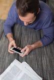 Man överföring av ett textmeddelande på hans smartphone Royaltyfria Foton