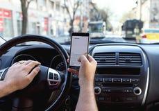 Man överföring av meddelandet från en smartphone, medan körning av en bil kan ca Royaltyfria Bilder