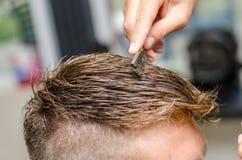 Man& x27 вырезывания парикмахера; волосы s с toothed бритвой Стоковая Фотография RF