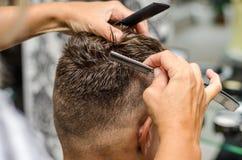 Man& x27 вырезывания парикмахера; волосы s с toothed бритвой Стоковая Фотография