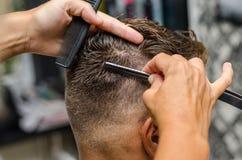 Man& x27 вырезывания парикмахера; волосы s с toothed бритвой Стоковое Изображение RF