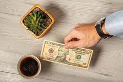 Man& x27; рука s дает долларовую банкноту 10 в оплате для чашки кофе Стоковая Фотография
