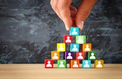 man& x27; рука s держа верхнюю часть деревянной пирамиды блоков с значками людей над деревянным столом Стоковые Изображения RF