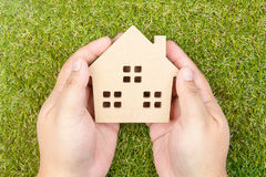 Man& x27; рука s держа деревянную игрушку дома на земной зеленой траве с c Стоковое Изображение RF