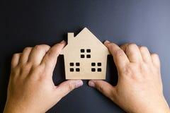 Man& x27; рука s держа деревянную игрушку дома на черной предпосылке с полисменом Стоковые Изображения