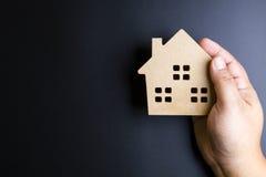 Man& x27; рука s держа деревянную игрушку дома на черной предпосылке с полисменом Стоковые Фотографии RF