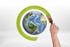 Man& x27; рука s обводит краску глобуса зеленую с щеткой Стоковое Фото