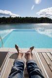 man& x27; 在懒人的s脚在游泳池旁边 免版税库存照片