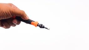 Man& x27; 拿着有橙色颜色把柄的s手螺丝刀 库存照片