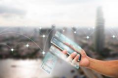 Man& x27; 拿着有透明多屏幕的s手智能手机在被弄脏的城市背景 库存图片