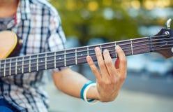 Man& x27; 有音响低音吉他的s手 库存照片