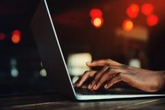 黑man& x27; 键入在键盘的s手 人与膝上型计算机一起使用 作为背景的美好的光 定调子 免版税库存照片